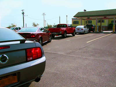 Cars wait in line at bank with engines running, wasting fuel an polluting air